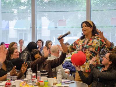 Woman speaking in front of community members