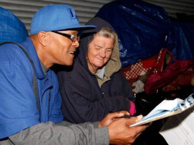 Man surveying homeless woman