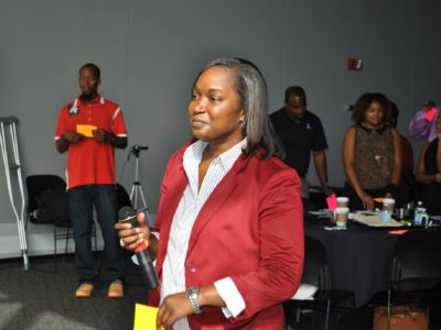 Young woman in red suit holding microphone