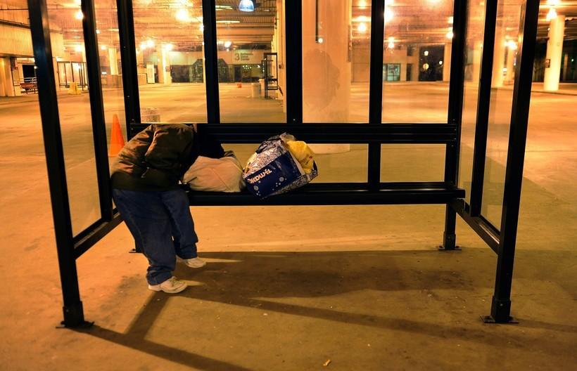 Man sleeping at bus shelter