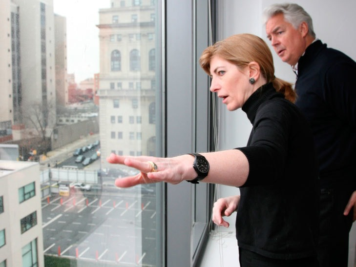Photo of Rosanne explaining the mission at a window