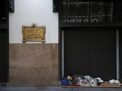 Homeless man sleeping outside of Macy's