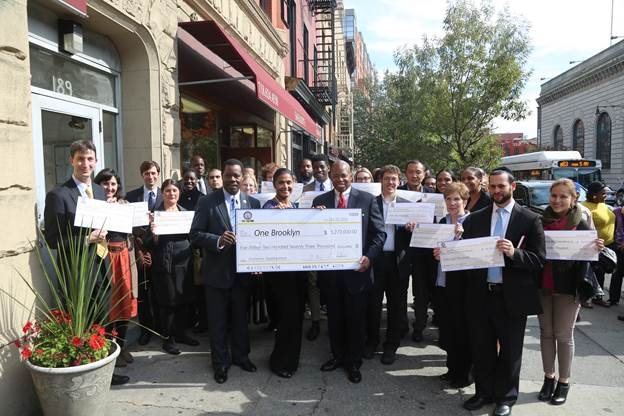 Man holding oversized check for One Brooklyn