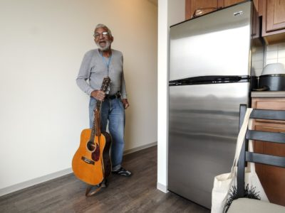 Newly-housed former homeless man in new apartment