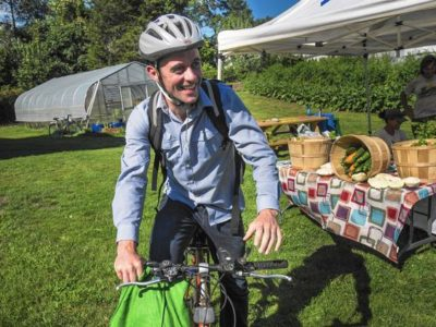 Man arriving to farmers market on bike