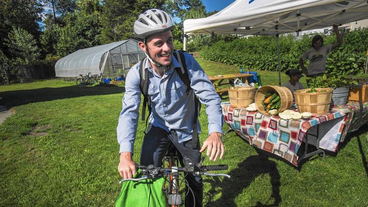 Man arriving to farmers market on bike