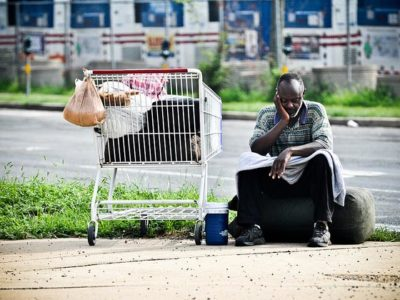 Homeless man sits with shopping cart