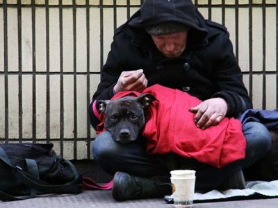 Homeless man sitting outside with dog