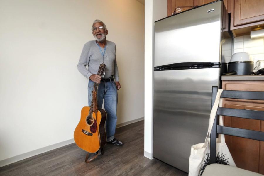 Man holding guitar in new housing