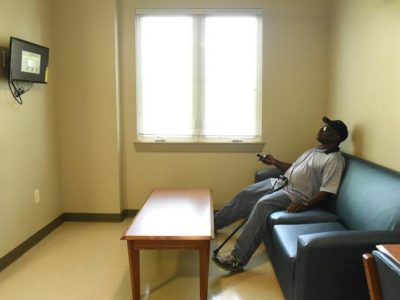 Man watching TV in new housing