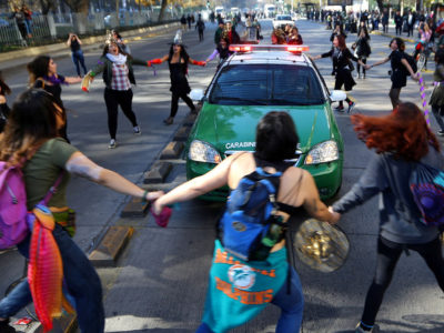 Young people circling police car