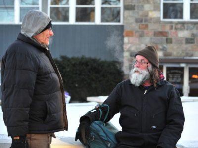 Homeless men talking outside in winter coats