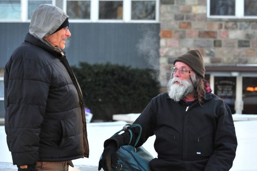 Homeless men talking outside in winter coats