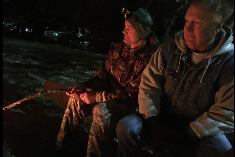 Adult men sitting by fire