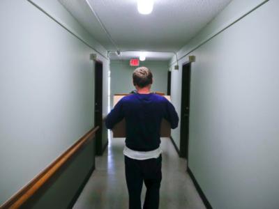 Man walking through hallway holding boxes