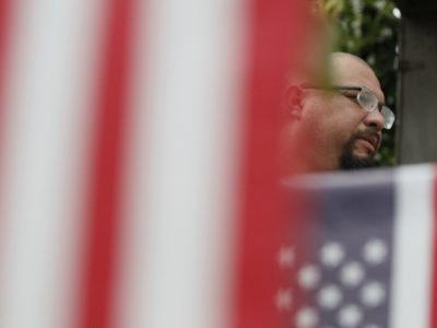 Veteran stands behind flag