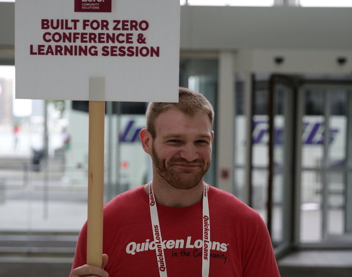 man holding conference sign