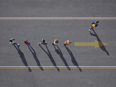 People walking in line on road, painted on asphalt, one person walking off.