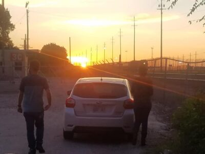 Outreach workers walking from car into sunset