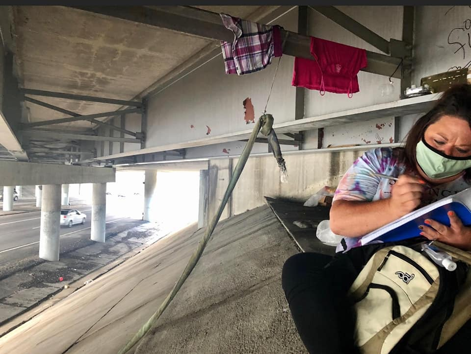 Outreach worker under overpass with mask on