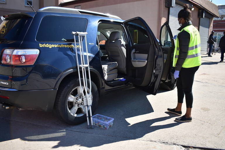 A Bridges staff members brings an unsheltered ciient to temporary housing.