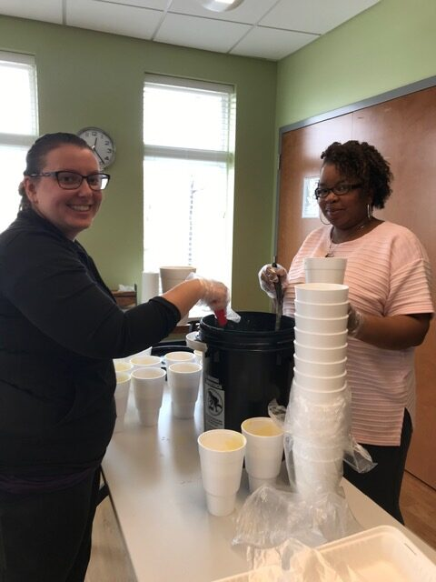 Javon Harris, Director of Supportive Housing, Beds Plus Care, and Supportive Housing Team Lead Jennifer Tudor preparing lunch for over 100 clients in hotel