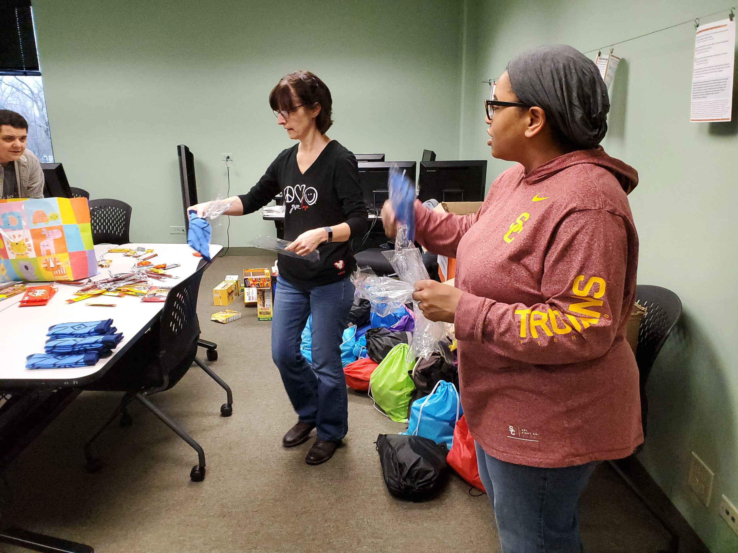 Lynn Suchwalko from Suburban Cook County's HMIS team and Kathryn Primas CoC Program Coordinator, Alliance to End Homelessness in Suburban Cook County preparing for the PIT Count by packing backpacks of supplies.