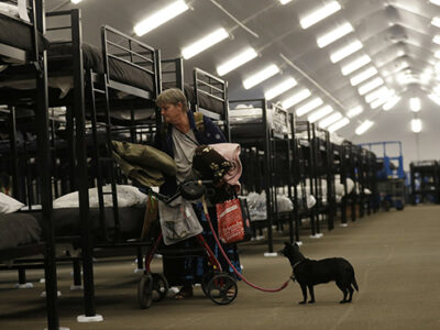 Woman and dog in homeless shelter (AP Photo/Gregory Bull)