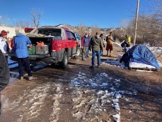 Outreach team walking by tent and truck on wintry day