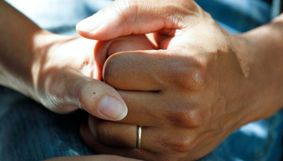 Hands clasped together, credit: American City and County Magazine
