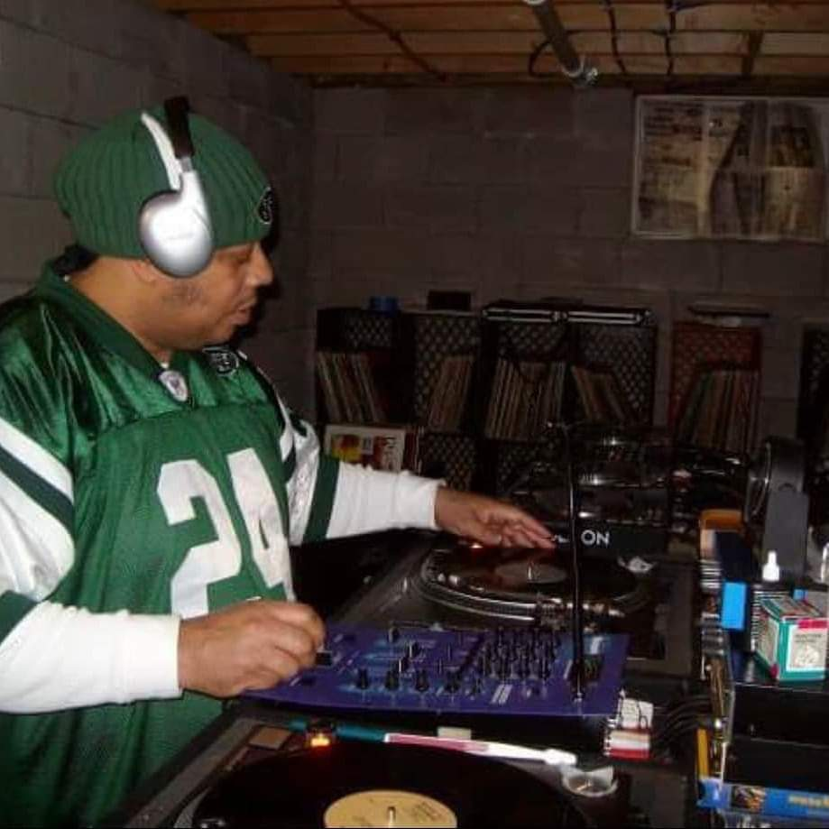 Richard at DJ booth with headphones on