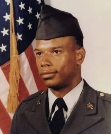 Headshot of a younger Richard in Army uniform in front of American flag