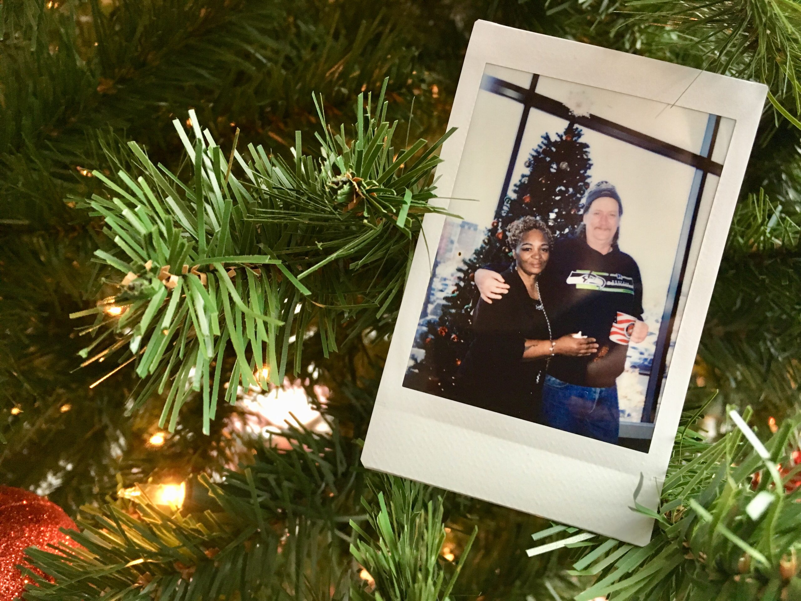 Polaroid photo hanging on Christmas tree featuring Paul and friend